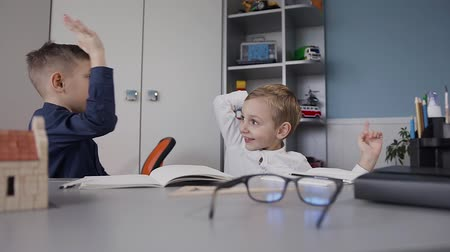 tél : The guys did their homework and gleefully splashed each other in their palms. Children sit at the desk at home in the white room. Schoolboys doing a lessons at home