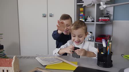 schoolkid : Two small children sitting at the table in the white room and have fun using the free internet network through the wireless connection in the phone Stock Footage