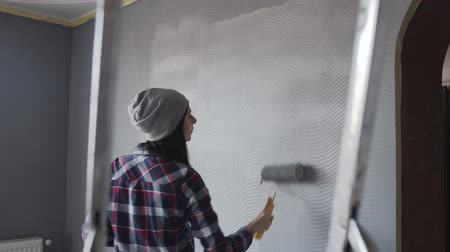 обновление : A beautiful hipster girl in a gray hat draws a wall with a roller in gray colo in her room , listens to music from the phone in headphones and dancing