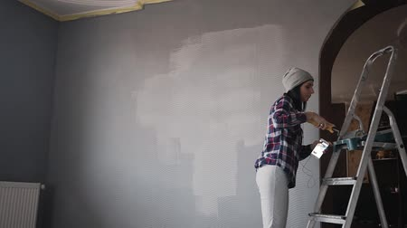 pedreiro : Beautiful young girl makes repairs in the apartment and listens to music and dancing, woman doing wall painting Vídeos