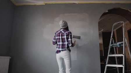 decorador : The girl painting wall with roller in the room with a gray paint she stands opposite that wall and dances while listening to music in the headphones from the phone