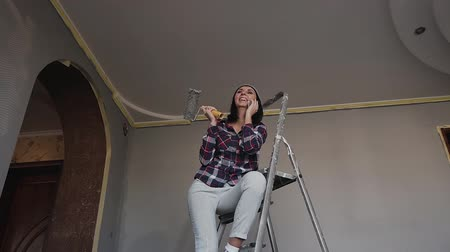 drabina : A beautiful young girl is sitting on the ladder, having fun talking on the phone and holding a roller in the hand that whitens the walls in his room. Woman painting her wall in gray