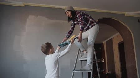praca zespołowa : A young woman standing on a ladder near the wall, her son gives her a container with a gray paint and a roller so that she could change the color of the wall. Repair in the house. Whitewashing the walls