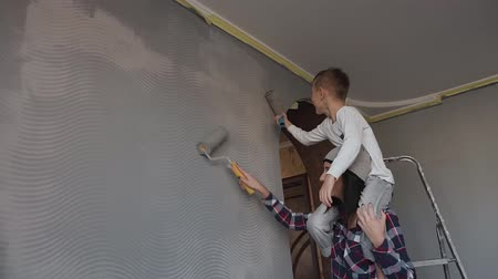 decorador : Sister with brother draw wallpapers on the wall in gray color roller in their room. Repair in the apartment