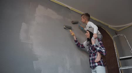 apartament : Young mother holds her son in her arms and the son paints a top wall with a roller in a gray color. Sister and brother draw wallpaper on the wall in gray color