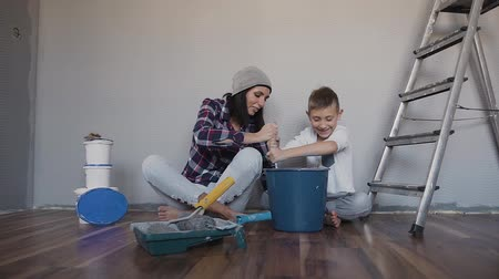 remodelar : A woman and child sit on the floor near the wall and mix the paint with a mixer in the bucket. Repair in the apartment. The painter blows the walls Stock Footage