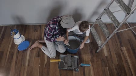próximo : Top view. The woman and her son sit on the floor near the wall next to the ladder and mix the paint with mixer in a bucket. Repair in the apartment