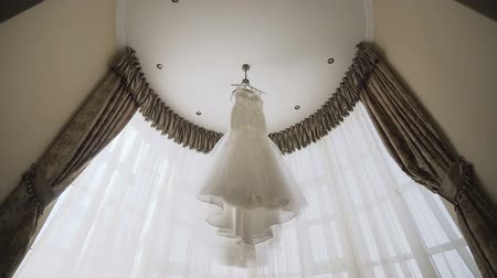 parte : A beautiful wedding white dress hanging on in a room near a large window Stock Footage