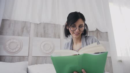 senta : Medium plan. Beautiful student in eyeglasses reading a fun book at home. The girl smiles while reading the book on the bed in the white bedroom. Morning light, concept of emotions
