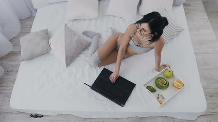senta : Top view of young beautiful girl with short hair sitting in bed in underwear, stockings and using laptop. Freelance typing on laptop. Healthy breakfast on tray on bed