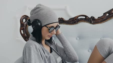 duygusallık : Close up. Young girl sits on the sofa wearing black headphones and listening to music from the phone. Hipster woman wearing sunglasses and gray hat. Indoor, in white background