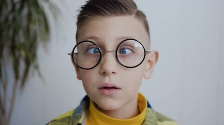 astigmatism : Close-up of the face of a little boy who has strabismus eyes and poor eyesight and he wears glasses to see better. The boy has blue eyes. In white background