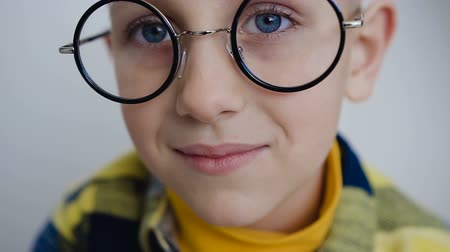 в середине : Close-up face of a lovely boy in glasses with beautiful blue eyes that look into the camera. Little boy has blue eyes and wearing stylish glasses. In white background Стоковые видеозаписи