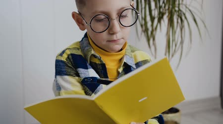 çivit : A stylish school boy wearing glasses sits on the background of a white wall and makes interesting notes in a notebook. A conceived boy makes notes in a yellow textbook. Indoors Stok Video