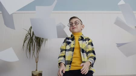 oturur : A beautiful boy throws a lot of paper up. The young man sits on a white background in his glasses. Stok Video