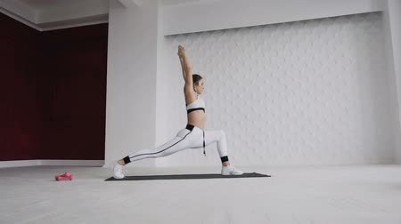pain free : Side view of beautiful young girl dressed in white sportswear, doing is yoga or pilates exercise in indoors on white background