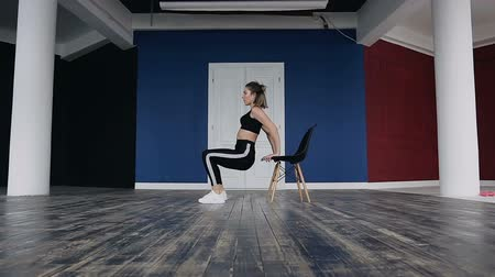 capa dura : Sports girl performs exercises with squatting leaning hands around on the chair. A young fitness woman trains performing exercises for her legs. Healthy way of life, workout. She dressed in black sportswears Vídeos