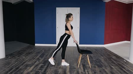 holding onto : Fitness young woman dressed in dark sportswear is training at the gym alone. She is doing one of the kind of push ups by holding onto the chair. Keeping yourself strong and healthy
