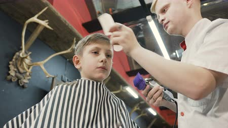 shaver : The hairdresser make a stylish haircut for a little boy in barbershop. Barber doing cutting hair with hair trimmer and comb. Mens hairstyling and haircutting in a barber shop or hair salon