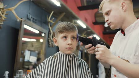 prádelník : Professional barber doing a new haircut with the help of ridge and electric shaver. Beautiful boy and stylist or hairdresser with trimmer doing haircut at hair salon or barber shop