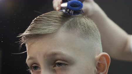 opatrný : Hairdresser makes hairstyle for boy with a hair dryer and a comb. Cute kid in barbershop. New hairstyle