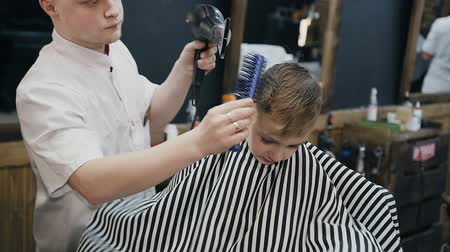 kurutma : Professional hairdresser drying hair of little boy with hairdryer and brush in barbershop. Wet hair little boy is dried by hairdryer. Barbershop Stok Video