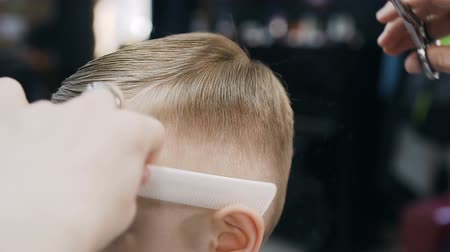 stroj : Close-up. Professional hairdresser makes a new haircut to the little boy. During haircuts barber uses an scissors and a comb. The guys haircut into a mans hairdressing salon,