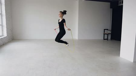 rhythmic : Mixed race. Skipping girl training at the gymnastics school working out is healthy fitness. Healthy teenage girl skipping with a jump rope. Sporting exercise, stretch, flexibility, aerobics