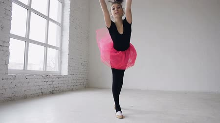 flexibility : Gymnastics school. Cute gymnast girl performs a backflip with hands in the spacious white ballroom. Flexible girl doing three acrobatic flips. Girl dressed in black bodysuit and pink skirt