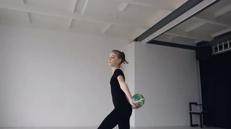 akrobatikus : Beautiful blonde girl dressed in black sports body suit performs dancing with ball in gymnastics school. Gymnast with the ball in his hands doing acrobatic moves at sport indoor in the white background