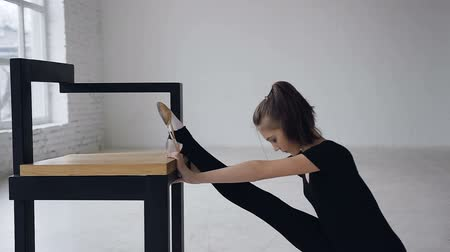 dietético : Cute slim girl doing stretching legs sitting in studio indoors. Attractive gymnast training flexibility, girl increases elasticity of muscles and improves mobility of joints. Proper stretching Stock Footage