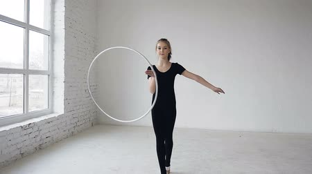 zasnoubený : Portrait of young attractive happy girl in black body spinning the hoop on the hand in the gymnastic school at white background and smiling on camera Dostupné videozáznamy