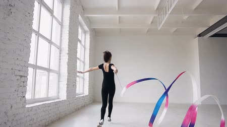 dividing : Blonde cute girl rhythmic gymnastics, modern with colored ribbon in black bodysuit in indoors at white bacground . Attractive gymnast girl jumping with ribbon in the gymnastics school or ballet school near big windows
