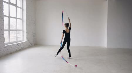 rhythmic : Rhythmic gymnast is holding ribbon in a hand and waving it and dance. She dressed in black body and is preparing for performance in a sports competition, looking at a camera