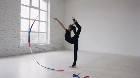 ритмичный : Little gymnastics in black body doing the gymnastics exercise with a colored ribbon in the white studio. Cute girl makes stretching exercise in sport gym.