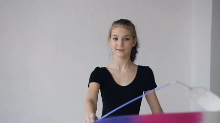 rhythmic : Portrait of cute graceful gymnastics spinning the colored ribbon in front of camera in the white studio Stock Footage