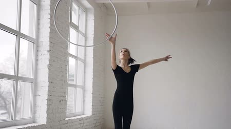 rhythmic : Portrait of cute attractive happy girl in black body spinning the hoop on the hand in the gymnastic school at white background and looking at the camera Stock Footage