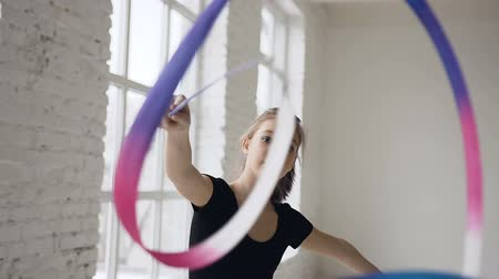 rhythmic : Portrait of graceful gymnastics spinning the colored ribbon in front of camera in the white studio on the window background and looking at the camera Stock Footage