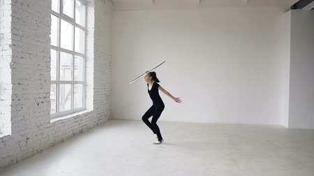 rhythmic : Young attractive girl in black body training a gymnastics exercise with a hoop in the sports school at white background