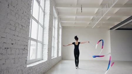 disciplina : Blonde cute girl dance rhythmic gymnastics, modern with colored ribbon in black bodysuit in front of the windows. Attractive female gymnast jumping with ribbon in the gymnastics school or ballet school