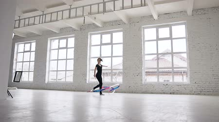 ритмичный : Rhythmic gymnastics: Girl in black body perform gymnastics exercise with a colored ribbon in sport school in windows background at gymnastics school. Ballet School. Workout