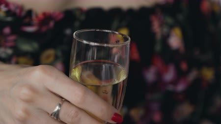 cheers : A glass of champagne in the young woman hand. The girl holds a glass of white wine in her hands. Glass of champagne in female hands