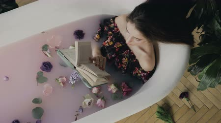 sen : Top view. A beautiful young woman reads a book and relaxing in a warm bath filled with milk and fragrant flower buds. Beautiful woman relaxing in milk bath lying in bathtub while reading an interesting book Wideo