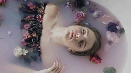 rejuvenescimento : Attractive girl in bath with milk and fragrant buds of flowers. Spa treatments for skin rejuvenation. Alluring woman in Spa salon. Pretty sexy young woman relaxing in jacuzzi with colored buds flower at spa centre Stock Footage