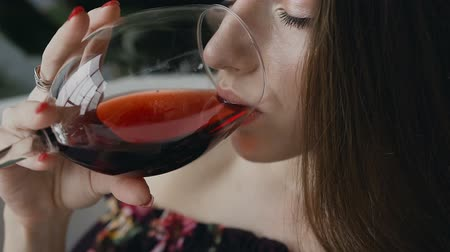 lápide : Close up. Beautiful young woman is drinking red wine in bath. Cute girl with a glass of red wine in her hand
