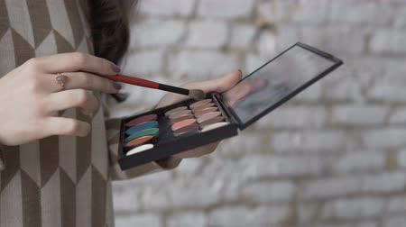 化粧品 : Close-up. A professional make-up artist picks up shadows on the brush. Make-up young woman artists hand with brush and eye-shadow palette
