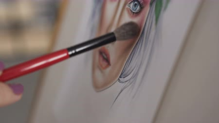 persone : Face chart. Closeup: hand of woman makeup artist who draws a face chart using the brush for cosmeticks and palette of shadows