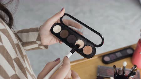 eyeshade : Professional make-up shade. The girl holds the palette of eyeshadows in her hands and apply one of the shades to her brush. Makeup shadows in female hands Stock Footage