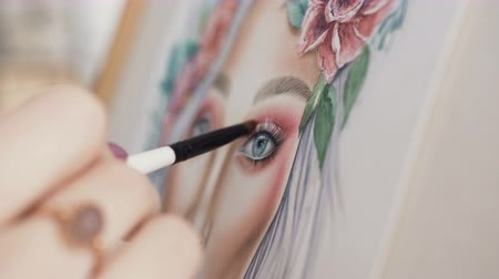 camsı : Make-up artist comes up with makeup using a face chart. The artist makeup paints face woman on paper and smears a small brush using palette of eyeshadows for eyes Stok Video
