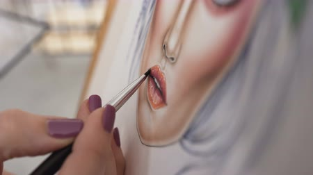melisa : Close-up view of an artists hand using special brush for drawing lips with lipstick. Professional makeup artist applying lipstick on face chart, working in beauty fashion industry
